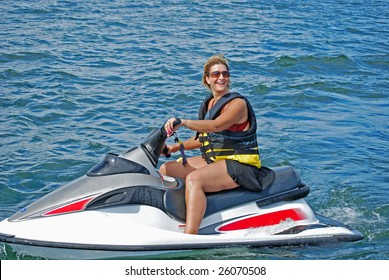 a woman enjoys a ride on a personal water craft on a beautiful summer day