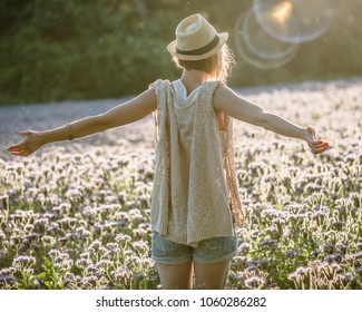 Woman enjoys summer with open arms at flower field.