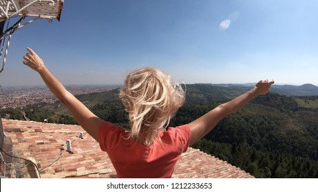 woman enjoys the top panorama of Bologna city from the tower viewpoint of the Madonna of San Luca Sanctuary on Bologna hills.