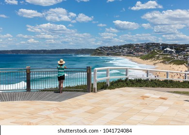 A woman enjoys the view of Bar beach - Merewether in Newcastle Australia. Bather's way is a newly developed coast walk in Australia's second oldest city a few hours drive north from Sydney.
