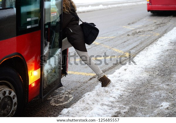 Woman entering bus in winter