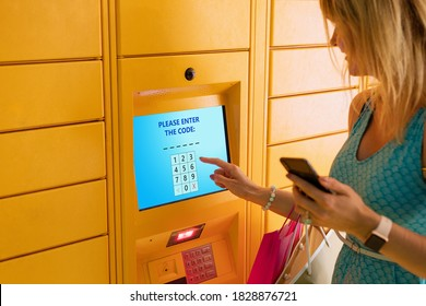 Woman entering code to receive parcel in post locker