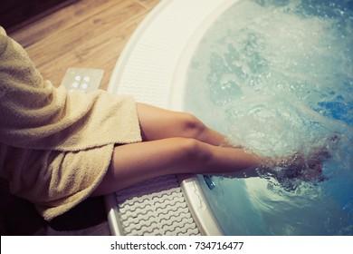 Woman entering hot tub in spa resort