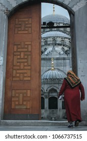 A woman entering a Mosque in Istanbul. A hidden gem of Islamic architecture as seen through a vintage door.