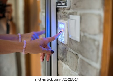 Woman entering password on home alarm keypad. Home security system.