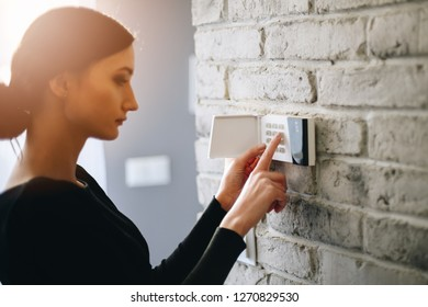 Woman entering security pin on home alarm keypad. Home security system