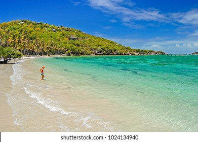 Woman entering water on secluded beach of Spring bay on Bequia Island, Caribbean Sea region of Lesser Antilles