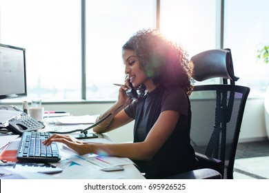 Woman entrepreneur busy with her work in office. Young woman talking over telephone while working on computer at her desk.