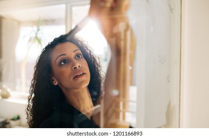 Woman entrepreneur discussing business ideas and plans on a glass board in office. Businesswoman writing on a transparent whiteboard in office.