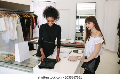 Woman entrepreneur making sale in her fashion boutique. Female storekeeper packing clothes purchased by customer.