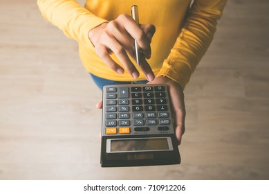 Woman entrepreneur using a calculator with a pen in her hand, calculating financial expense at home office