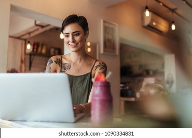 Woman entrepreneur working on laptop computer at home with a smoothie on the table. Woman with tattoos on her body working on laptop.