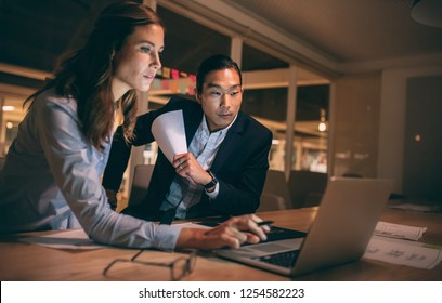 Woman entrepreneur working on laptop sitting with her colleague in office. Business partners working late night to meet project deadlines.