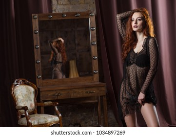 woman in erotic underwear stands touches his hair. scene of temptation. model posing near the mirror in the boudoir room.