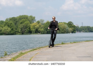 Woman with e-scooter is driving on the shore of a lake in the city