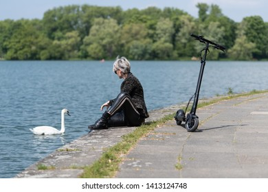 Woman with e-scooter is feeding swan by the lake