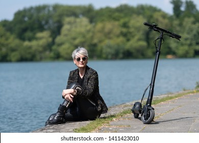 Woman with e-scooter relaxes at the lakeshore