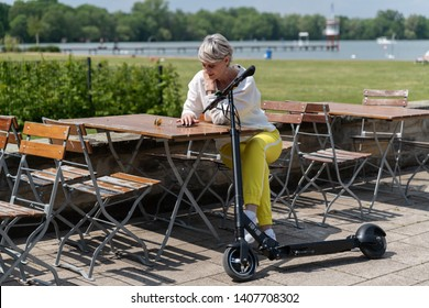 Woman with e-scooter sitting in a beer garden