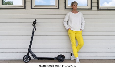 Woman with e-scooter is standing in front of a house