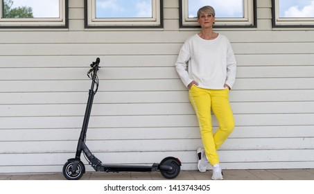 Woman with e-scooter is standing at house wall
