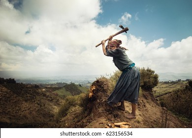Woman of Ethiopian origin chopping wood nearby Wenchi Crater Lake, Ethiopia, Africa on 28th of September 2016