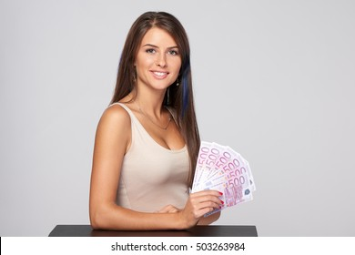 Woman with euro money paper currency in hand over grey background, with copy space