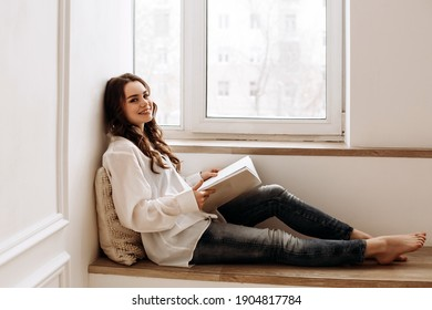 woman of European appearance reads a book. Portrait of a lady in a white shirt with a magazine in her hand. Woman sitting indoors by the window on the windowsill