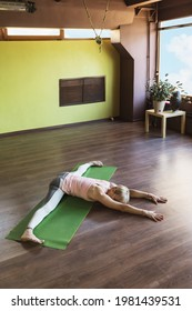 Woman of european appearance, in sportswear, practicing yoga, performs a samokanasana exercise on a mat, a transverse twine with a forward tilt of the body.