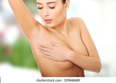 Woman examining breast mastopathy or cancer.