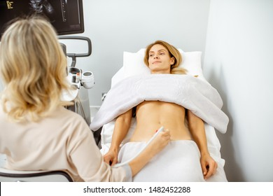 Woman examining her pelvic organs with ultrasound sensor or diagnosing early pregnancy at the medical office. Concept of ultrasound diagnostics of female health