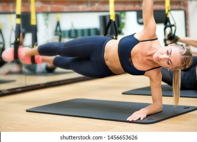Woman excersising suspended elbow side plank with trx at gym