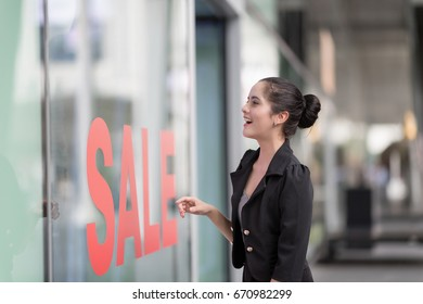 Woman excited looking into shop with shop window display with text SALE on red poster.Going shopping downtown concept