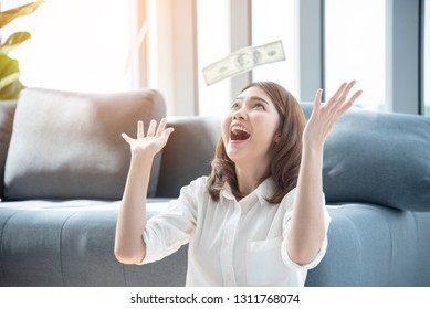 Woman excited with money dollar banknote rain fall. Happy start up business woman got winner lucky draw reward rich millionaire with happiness. Financial success woman investment.