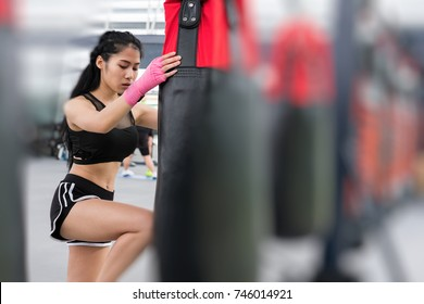 woman execute exercise in fitness center. female athlete hitting and punching sandbag with rowing machine in boxing gym. sporty asian girl working out in health club. martial arts, muay thai concept