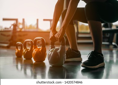 Woman in exercise gear standing in a row holding dumbbells during an exercise class at the gym.Fitness training with kettlebell in sport gym.
