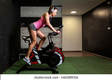 Woman exercise in gym on bike and liste music over headphones on her head