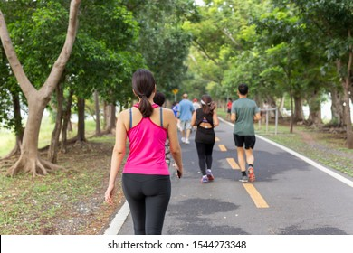 Woman exercise walking in the park with group people in blur background.