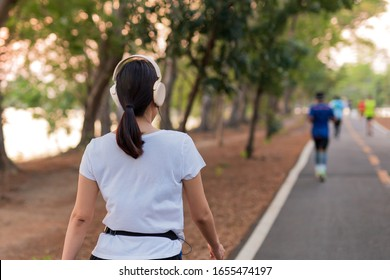 Woman exercise walking in the park listening to music with headphone