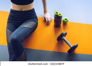 Woman exercise workout in gym fitness breaking relax with apple fruit after training sport with dumbbell and protein shake bottle healthy lifestyle bodybuilding, Top view
