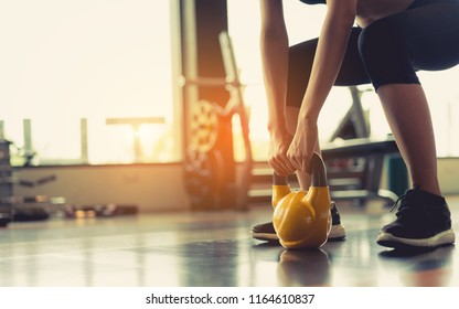 Woman exercise workout at gym fitness training sport with kettlebell weight lifting and legs squat healthy lifestyle bodybuilding.