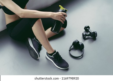 Woman exercise workout in gym fitness breaking relax holding protein shake bottle after training sport with dumbbell and headphone music equipment healthy lifestyle bodybuilding, Top view