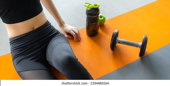 Woman exercise workout in gym fitness breaking relax with apple fruit after training sport with dumbbell and protein shake bottle healthy lifestyle bodybuilding, Top view.