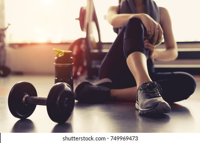 Photo of Woman exercise workout in gym fitness breaking relax holding apple fruit after training sport with dumbbell and protein shake bottle healthy lifestyle bodybuilding, Athlete builder muscles lifestyle.
