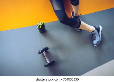 Woman exercise workout in gym fitness breaking relax holding apple fruit after training sport with dumbbell and protein shake bottle healthy lifestyle bodybuilding, Top view