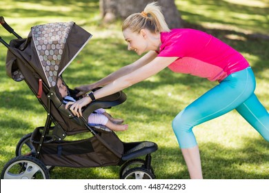 Woman exercising with baby stroller in park