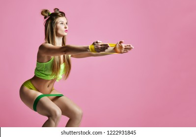 Woman exercising doing postnatal workout. Female fitness instructor working out with a rubber resistance band on modern pink background