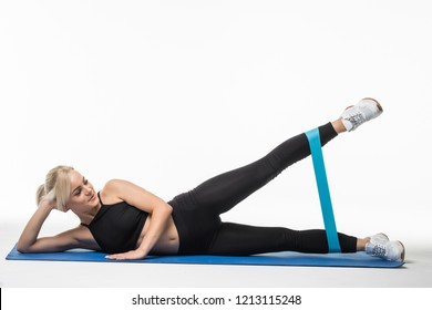 Woman exercising doing workout for legs with elastic bands lying on floor isolated on white background