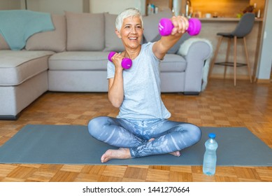 Woman Exercising With Dumbbell At Home. Feeling great inside and out! Age is no excuse to slack on your health. Portrait of smiling senior woman holding dumbbell