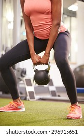 Woman exercising in a gym with a kettlebell weight, crop