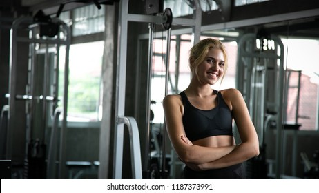 A woman exercising at a gym, she is happy and relaxed, she is smiling.